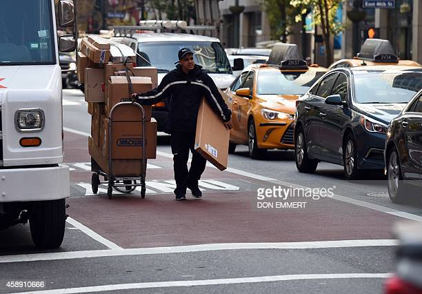 A delivery man moves boxes on carts up 3rd Avenue on November 13 2014 in New York The man used the near empty bus lane to navigate while heavy auto...
