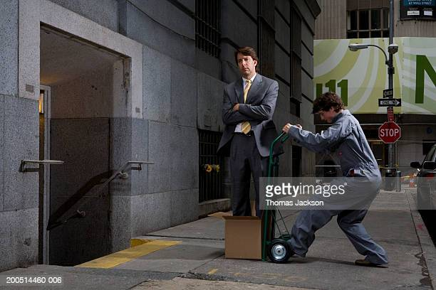 delivery man moving businessman in cardboard box on hand truck outside office building - downtown comedy duo stock pictures, royalty-free photos & images