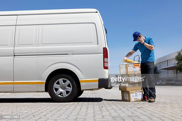 delivery man on phone - delivery person stock pictures, royalty-free photos & images