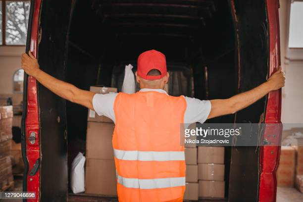 delivery man opening delivery van - pallet industrial equipment stock pictures, royalty-free photos & images