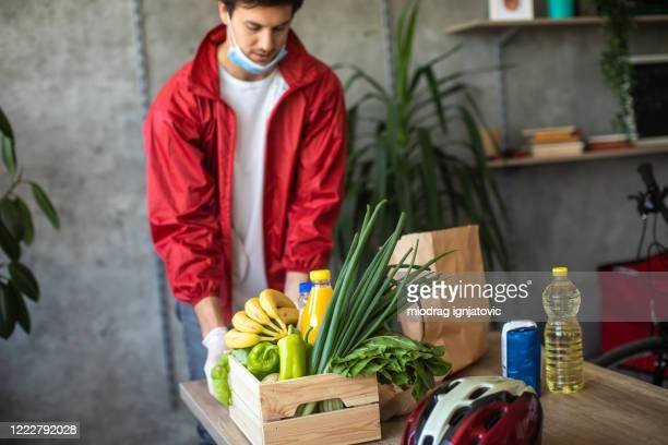 delivery man packing food for delivery  during covid-19 pandemic - saco objeto manufaturado imagens e fotografias de stock