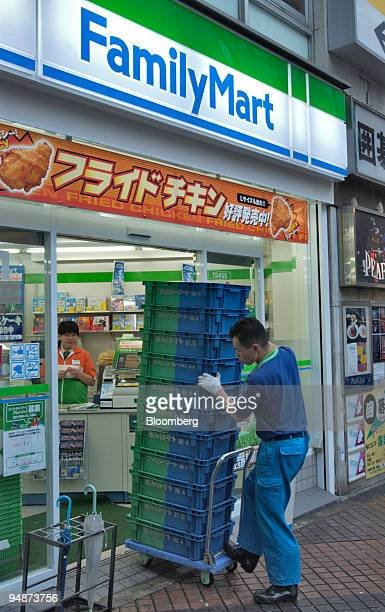 A delivery man pushes trays of food into a FamilyMart Co convenience store in Tokyo on October 13 2004 7Eleven Japan Co Lawson Inc and rival...