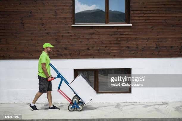 delivery man pushing dolly to home delivery. - sack barrow stock pictures, royalty-free photos & images