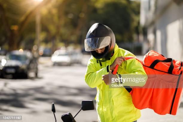 entregador removendo sua mochila - motoboy - motocicleta - fotografias e filmes do acervo