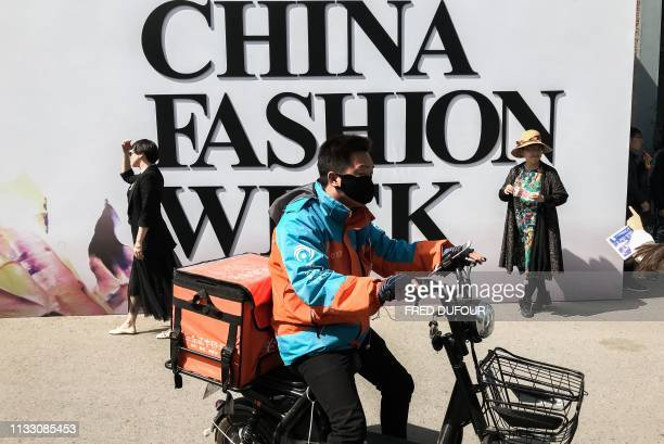 Delivery man rides his bike past guests posing for a picture during the China Fashion Week in Beijing on March 27, 2019.