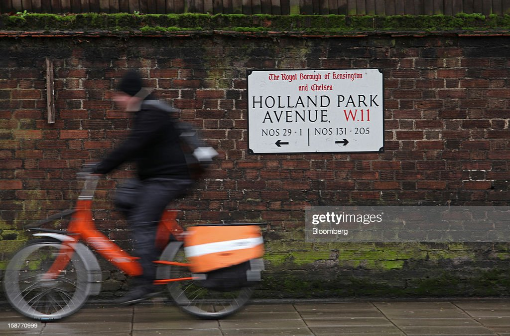 A TNT delivery man rides past a street sign on Holland Park Avenue in the Kensington and Chelsea borough of London, U.K., on Friday, Dec. 28, 2012. Egerton Crescent, close to Harrods luxury department store in Knightsbridge, is the most expensive address in the borough, with an average property value of 8.14 million pounds ($13.2 million), Lloyds TSB said. Photographer: Chris Ratcliffe/Bloomberg via Getty Images