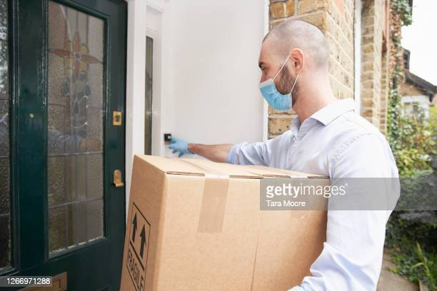 delivery man ring doorbell at house - residential building stock pictures, royalty-free photos & images