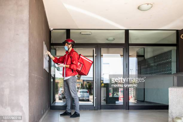 delivery man ringing on intercom and waiting for customer - intercom stock pictures, royalty-free photos & images