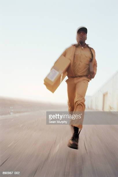 Delivery man running with package, low angle view (blurred motion)
