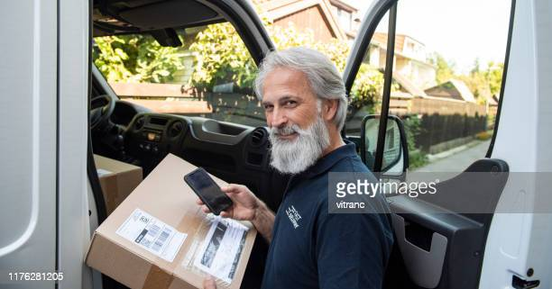 delivery man scanning barcode on smart phone - time of day stock pictures, royalty-free photos & images