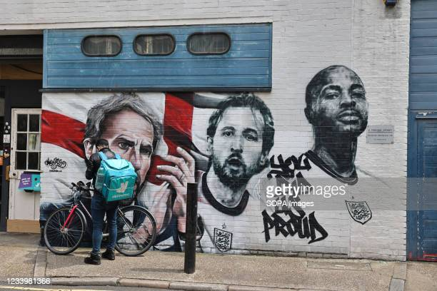 Delivery man seen in front of the mural of England football manager Gareth Southgate and players Harry Kane and Raheem Sterling, with the words 'You...