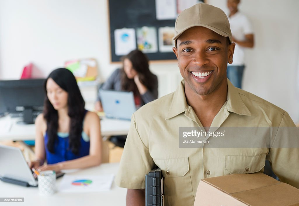 Delivery man smiling in office : Foto stock