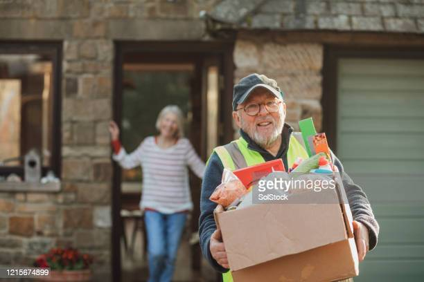 delivery man smiling - volunteer stock pictures, royalty-free photos & images