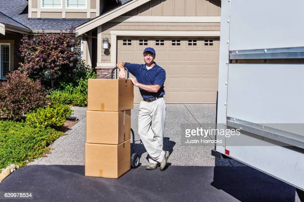 Delivery Man Standing with Boxes on a Hand Truck