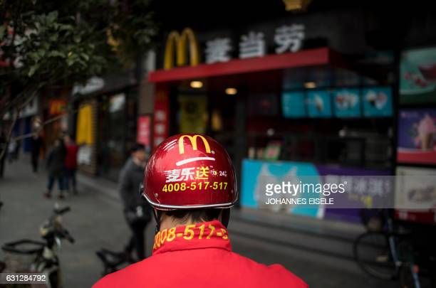 A delivery man stands in front of a McDonald's fast food restaurant in Shanghai on January 9 2017 US fastfood giant McDonalds will sell a controlling...