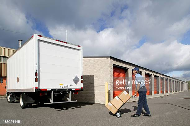 delivery man taking boxes to the truck on a dolly - storage compartment stock pictures, royalty-free photos & images