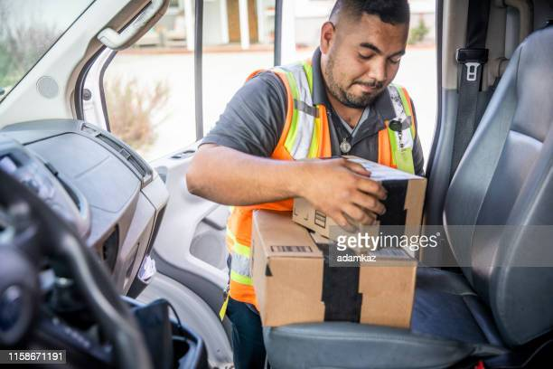 delivery man taking packages from vehicle - home delivery stock pictures, royalty-free photos & images