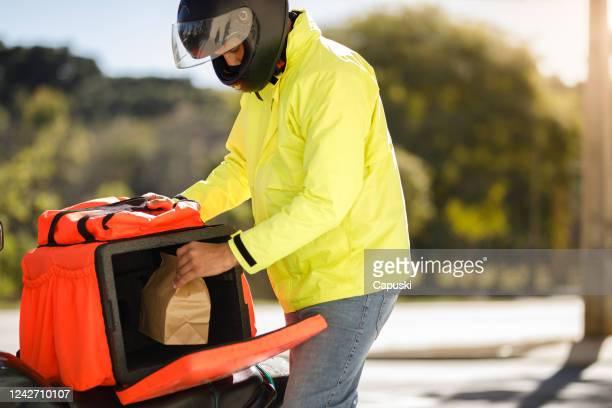 entregador tirando o pedido da mochila - motoboy - comida - fotografias e filmes do acervo