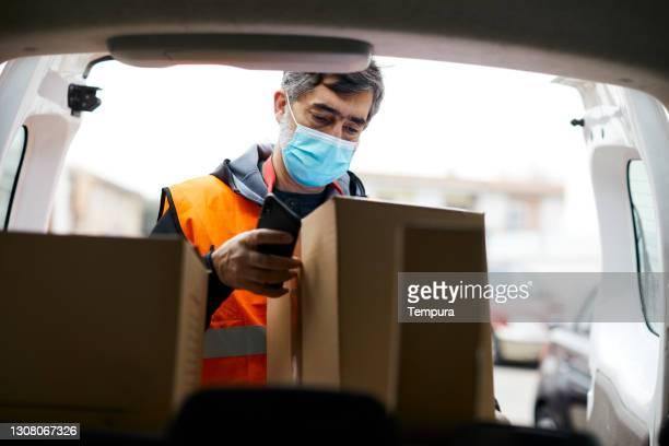 un repartidor subiendo paquetes a la furgoneta con una máscara protectora covid - sólo con adultos fotografías e imágenes de stock