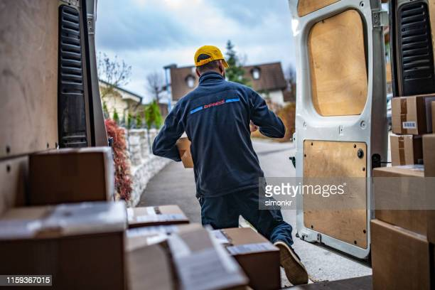 delivery man walking out of van - black jacket stock pictures, royalty-free photos & images