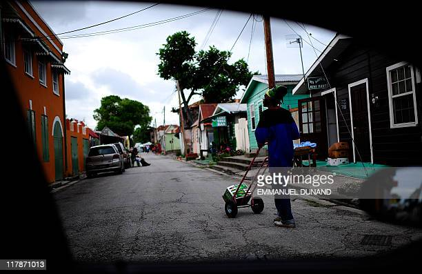 Delivery man walks down a street on his way to deliver a case of beer in Bridgetown, Barbados, June 30, 2011. AFP PHOTO/Emmanuel DUNAND