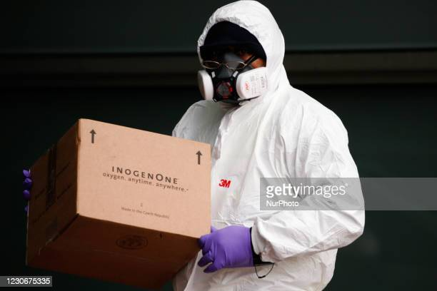 Delivery man wearing a PPE suit and respirator mask carries a package past ambulances outside the emergency department of the Royal London Hospital...