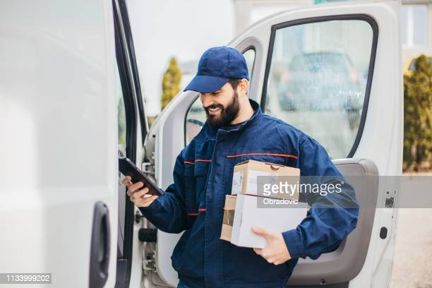 delivery man with a parcel box in the car. - stock image... save - delivery person stock pictures, royalty-free photos & images