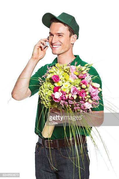 delivery man with flowers, talking on phone - izusek stock pictures, royalty-free photos & images
