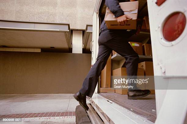 Delivery man with package stepping into truck