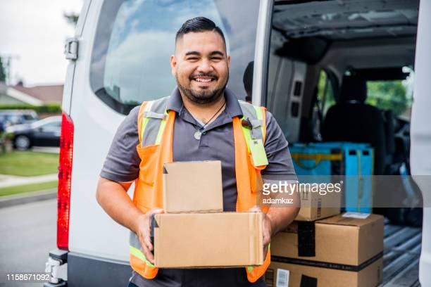 delivery man with packages - postal worker stock pictures, royalty-free photos & images
