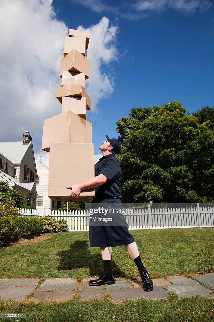 Delivery man with stack of boxes : Stockfoto
