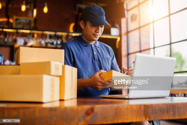 delivery man work out online shopping at her home with a laptop. - market retail space stock photos and pictures