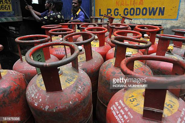 Delivery men stand next to LPG cylinders at a warehouse in Mumbai on September 14 2012 India's government was confronted by strike threats and a...