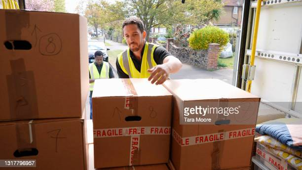 delivery men unloading boxes from van - offloading stock pictures, royalty-free photos & images