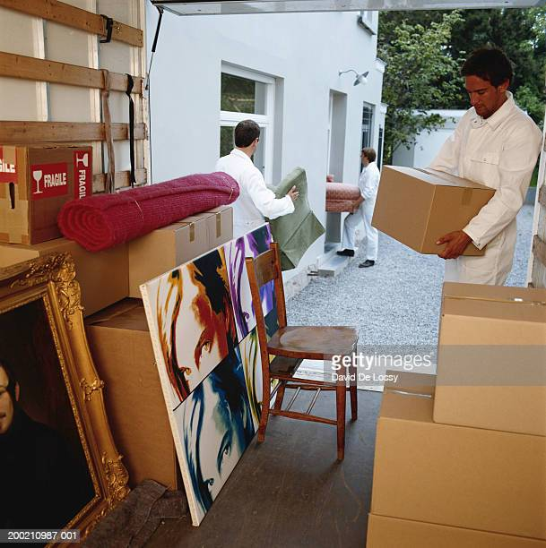 Delivery men unloading household thing from van