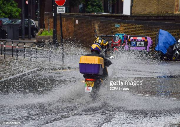 Delivery motorcyclist splashes through a flooded Farringdon Lane in central London after a day of heavy rain in the capital.