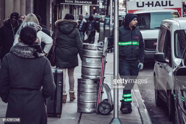 Delivery of aluminium kegs of beer with sack truck in New York street
