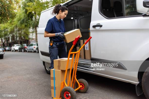 delivery person checking the boxes and loading on a hand cart - sack barrow stock pictures, royalty-free photos & images
