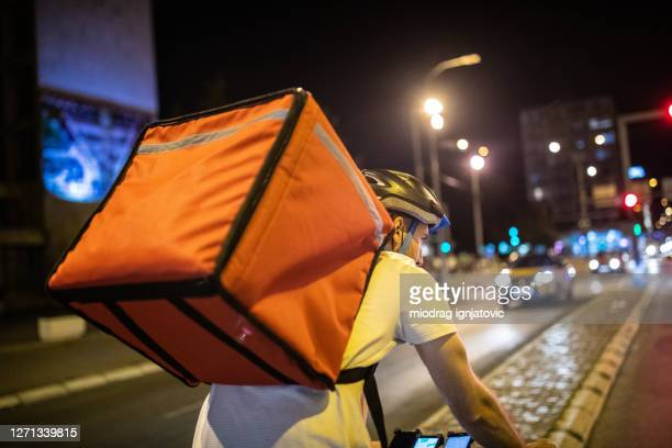 delivery person cycling through city streets on his way to customer at night - evening meal imagens e fotografias de stock