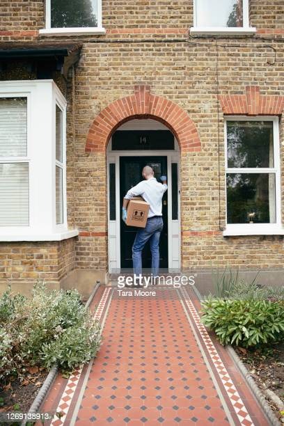 delivery person knocking on door at house - parcel stock pictures, royalty-free photos & images