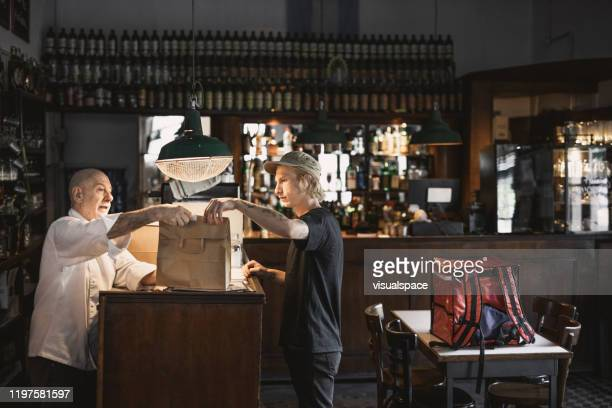 delivery person receiving order in a restaurant - take out food stock pictures, royalty-free photos & images