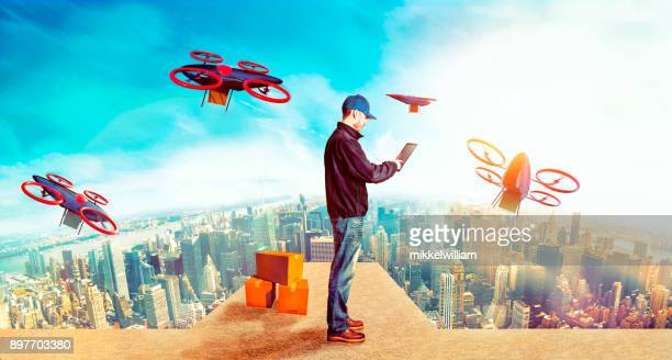 Delivery person sends off drones with packages from skyscraper in future city