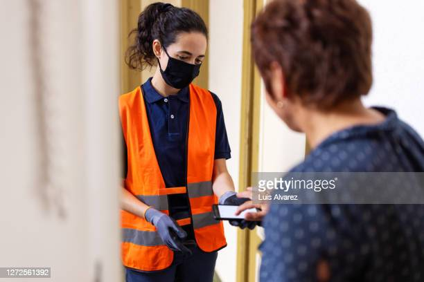 delivery person taking signature from customer after delivering the package - essential workers stock pictures, royalty-free photos & images