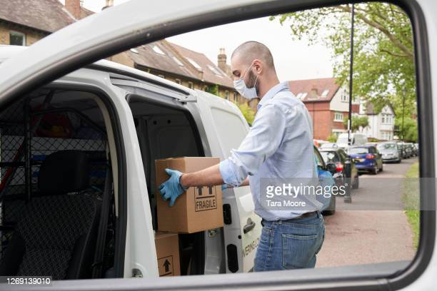 delivery person unloading box from van - working stock pictures, royalty-free photos & images