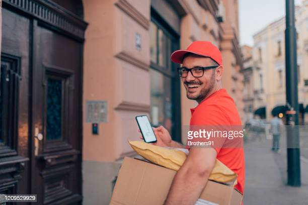 delivery person using a mobile phone - uniform cap stock pictures, royalty-free photos & images