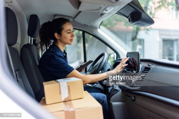 delivery person using car gps to determine customer's address - driving stock pictures, royalty-free photos & images
