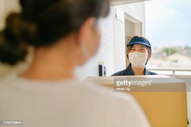 保護フェイスマスクを着用し、衣装に荷物を配達する配達員 - 建物入口 ストックフォトと画像