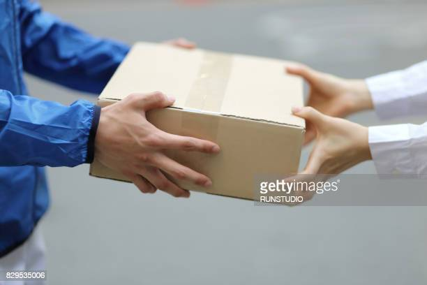delivery person with packages,close up - giving stock photos and pictures