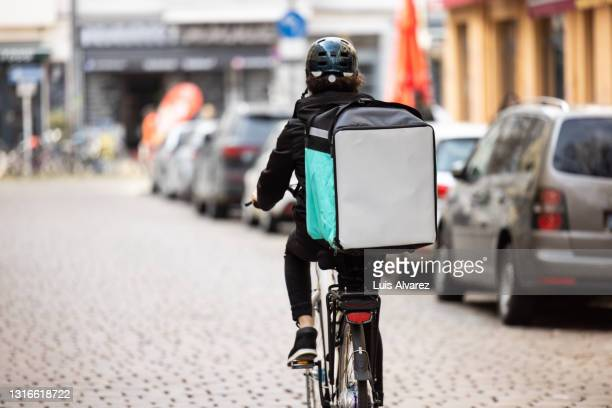 delivery person with thermal box on a bicycle in town - essential services stock pictures, royalty-free photos & images