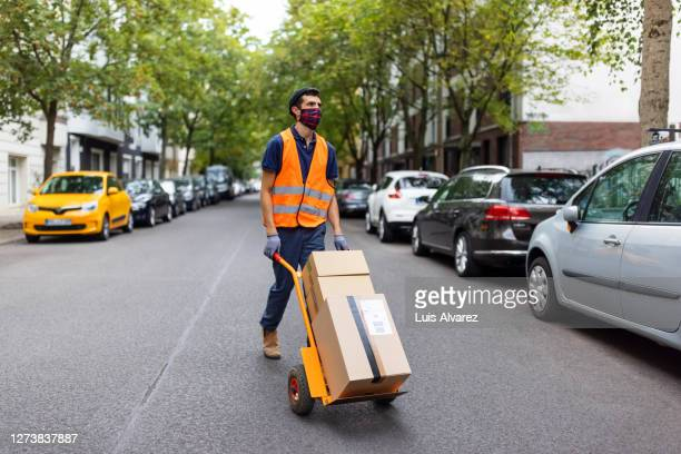 delivery person working during pandemic - sack barrow stock pictures, royalty-free photos & images